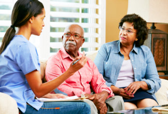 senior couple talking with caregiver