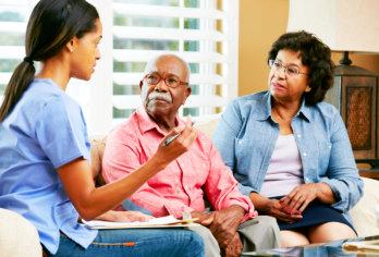 senior couple talking with caregiver